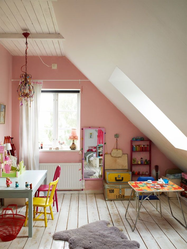 Upstairs play area -- gorgeous play room for kids -- faux animal rug, skylight, pink walls, white wood floor, fun chandelier, red and yellow chairs, blue table, vintage luggage, old suitcases, stuffed puppy, fold out table, pink lampshade, tea set, ukulele, red basket -- what other fun things can you find?