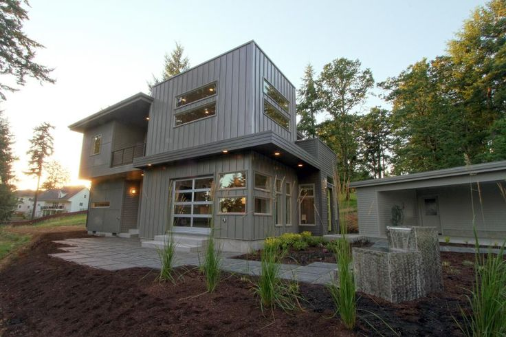 This modern home features box shapes, long windows and a gray tone which is a beautiful contrast against the natural colors from the surrounding yard. A stone walkway leads from the house through the garden area.