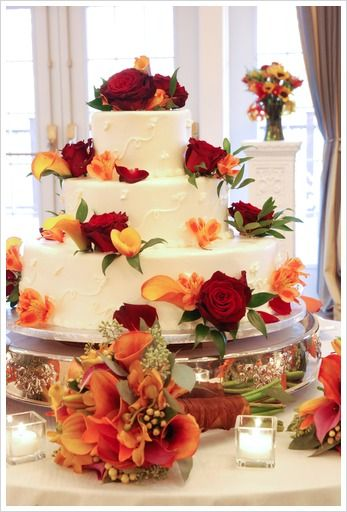 Fall Theme Wedding Cake 3 Tier A white wedding cake decorated with dark red roses, flame calla lilies and orange alstromeria blooms. Also added were some ruscus leaves for a more natural look.