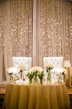 Who says you need regular dining chairs? Find a pair of plush chairs, and sit comfortably on your newlywed thrones. A collection of flower arrangements in vases and cascading beads as a backdrop complete the soft yet chic look.
