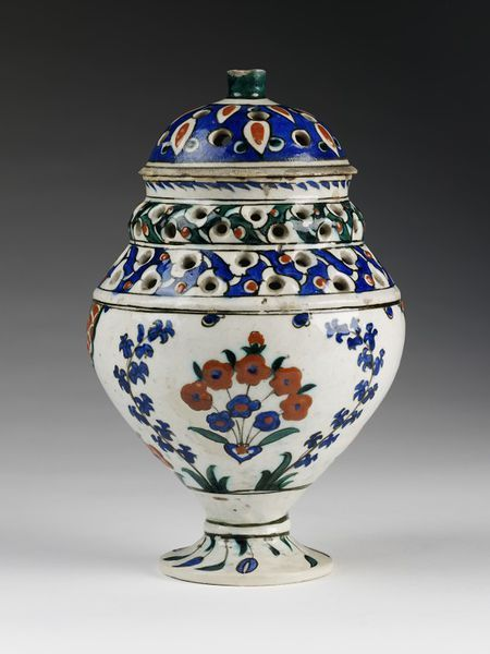 Vase and cover Place of origin: Iznik, Turkey (made) Date: ca. 1600 (made) Physical description Perfume-vase and cover of fritware, the cover and margin of the vase perforated, the body painted with red and blue flowers.
