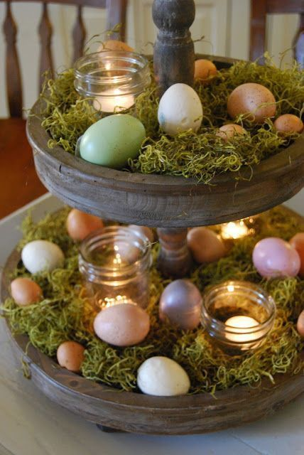 Spring table centerpiece with colored Easter eggs, candle jars, and grass