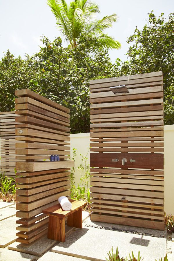 Wood-paneled outdoor showers in the Deluxe Beach Villas at Viceroy Maldives.