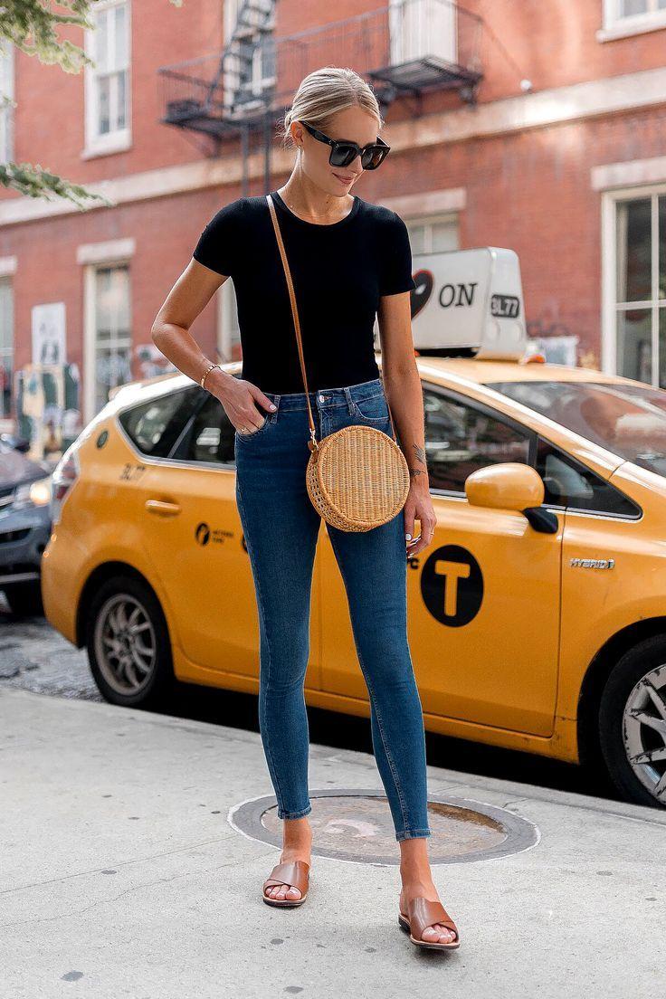 Blonde Frau mit Bloomingdales Schwarzer Kurzarm-Body Denim Skinny Jeans Beige Flache Sandalen Kreis Strohhandtasche Schwarze Sonnenbrille Mode Jackson Dallas Blogger Mode-Blogger New York Street Style