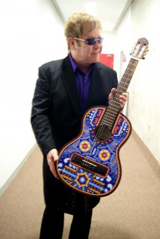 Acoustic guitar decorated with Huichol art from Mex.