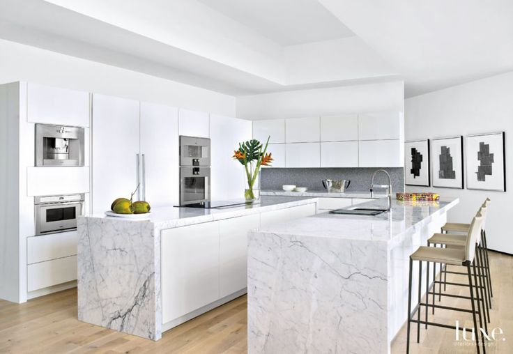 The kitchen's all-white theme—including cabinetry fabricated by Arkin Construction—keeps the space as light as a cloud, while an Avonite backsplash by Aristech Surfaces and Gaggenau ovens from Monark offer contrast. The Carrara marble countertops, from Modern Interior Mall, were fabricated by Elegance Marble and Granite of Fort Lauderdale. Pencil-legged barstools by Zanotta continue the modern scheme.
