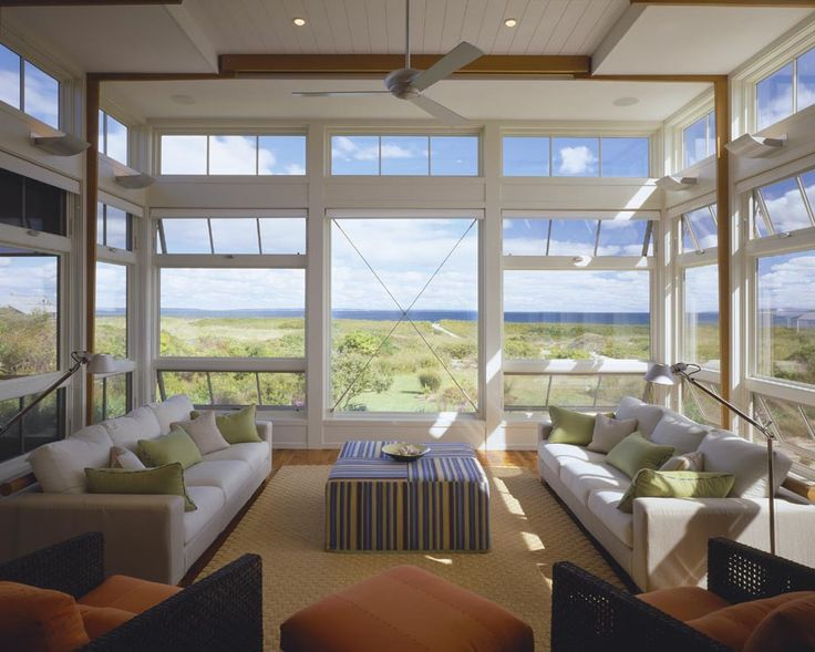 spectacular beach house living room:otto;  exceptional windows; use of transoms; functional windows at bottom; contemporary ceiling fan; neutral sofas (don't compete with view); unique ottoman fabric; sisal