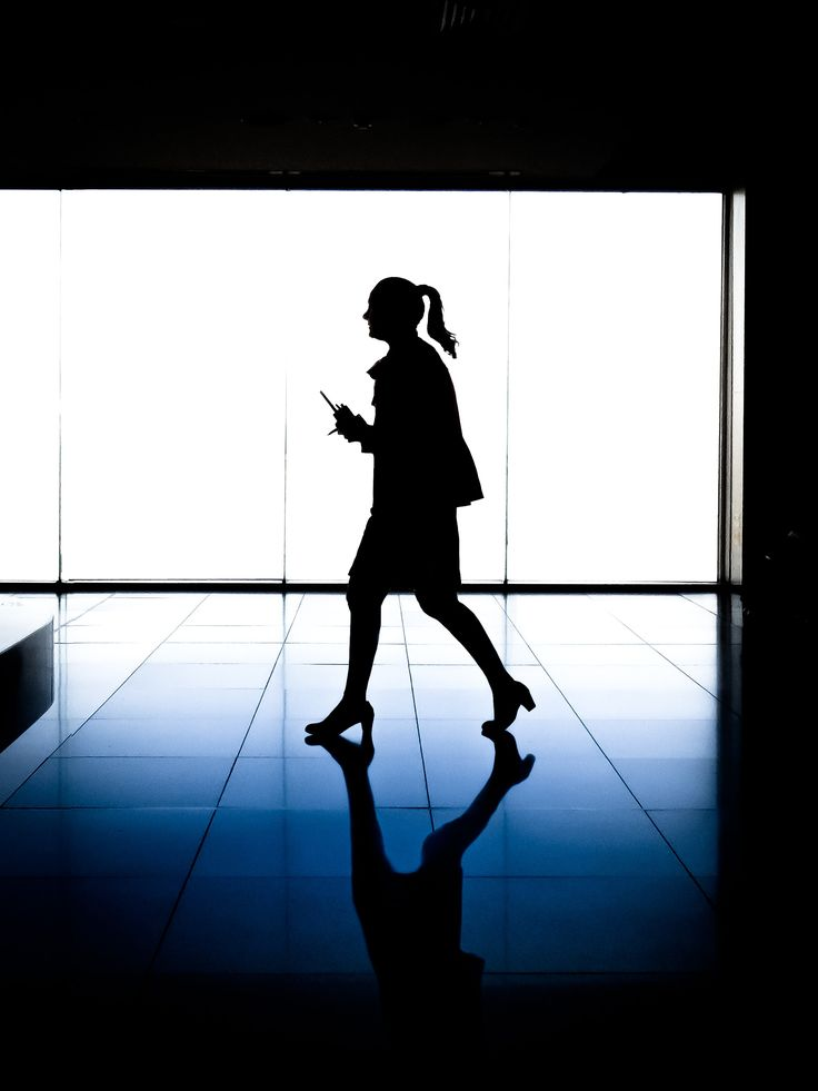 A silhouette of a woman walking through a building at Melbourne Airport