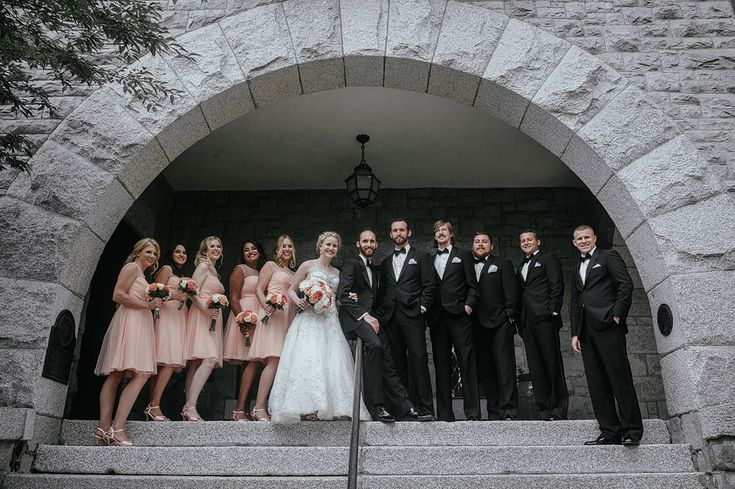 Matt Shumate Photography at Glover Mansion summer wedding. Wedding party standing on top of the step under stone wall archway. Bridesmaid are wearing peach color dress and shoes holding white and peach colored flower bouquets