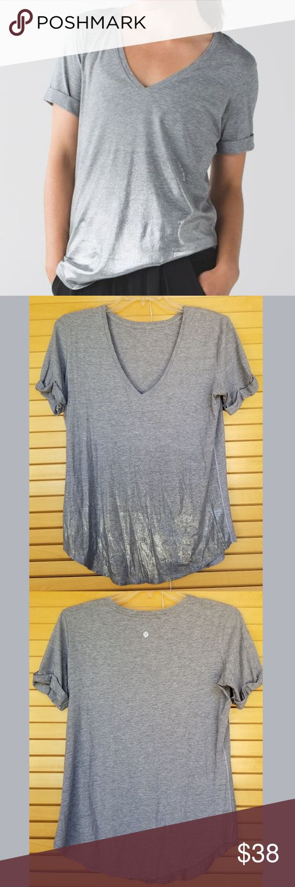 Lululemon Love Tee II in heathered grey w/ silver You can wear this tee anywhere! The soft fabric feels great against your skin and the curved hem is easy to tuck in.  Features Vitasea, which is soft with added LYCRA® fibre for great shape retention.  Wear the sleeves down or roll them up.  Designed not to shrink.  Designed for yoga/gym and to/from.  Loose fit and long length.  Great pre-owned condition.  Color is medium heathered grey and there's some metallic silver on the bottom front…