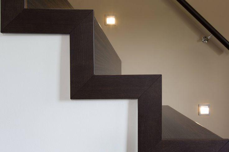 Moderne bloktrap in open ruimte gerenoveerd door de treden te bekleden met donkere houten overzettreden. In combinatie met een trapleuning ledverlichting.