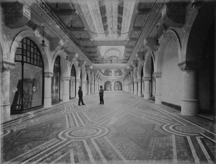 Interior view of men in the Queen Victoria Building, ground floor, showing the general layout and also details including joinery and glass work, carved stone columns, colonnaded shops and floor mosaic tiling. 1898
