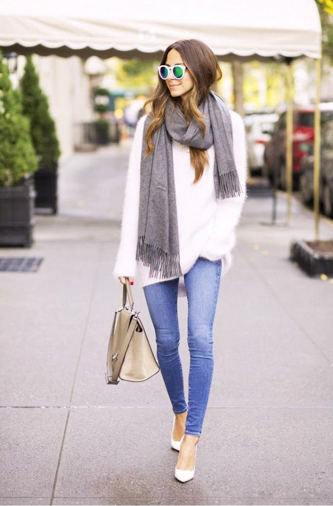 A white sweater is worn with a gray scarf, skinny jeans, white pumps, a neutral bag, and mirrored sunglasses