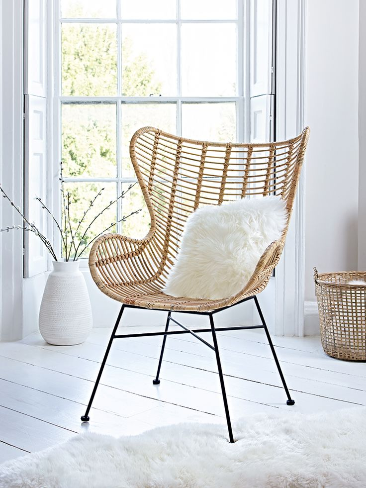 Woven from natural rattan with a strong metal frame, our large elegant chair has a wide seat curved, high winged back and low arms. This style statement is a nod to the 1950's with its blonde rattan details and black iron legs. The perfect occasional chair for your living space or bedroom, team this comfortable seat with something from our Sheepskins & Hides collection to complete the look.