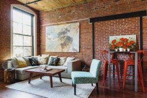 Diese industriellen Wohnzimmer genießt natürliche Beleuchtung von seinem weißen getrimmte große Fenster und Funktionen ausgesetzt roten Backsteinmauer. Foto: Homepolish