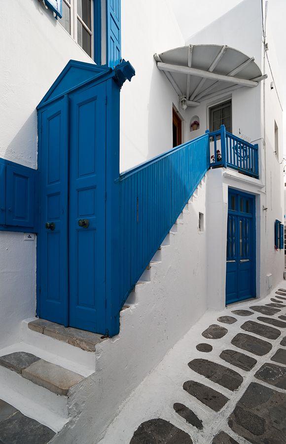 Streets of Hora - Mykonos, Greece. Blue stair railings. Blue doors. White buildings. Stone street.