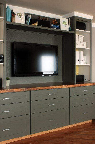 Entertainment center with storage drawers - wall painted behind tv same color as the wood