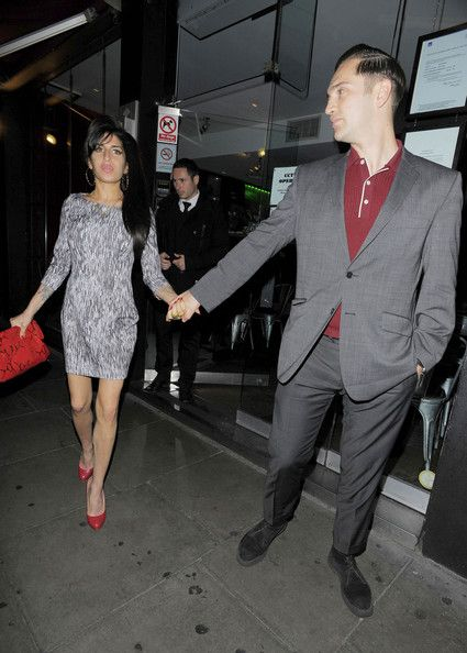 Amy Winehouse Photos Photos - Amy Winehouse struggles to get into the backseat of a car as she and boyfriend Reg Traviss leave Ballans Restaurant in London. REF: DBMJ. - Amy Winehouse at Ballans Restaurant