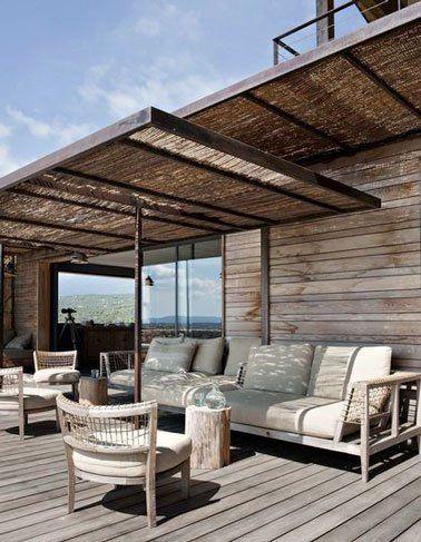 Une terrasse en bois avec une pergola en fer forgé et canisses