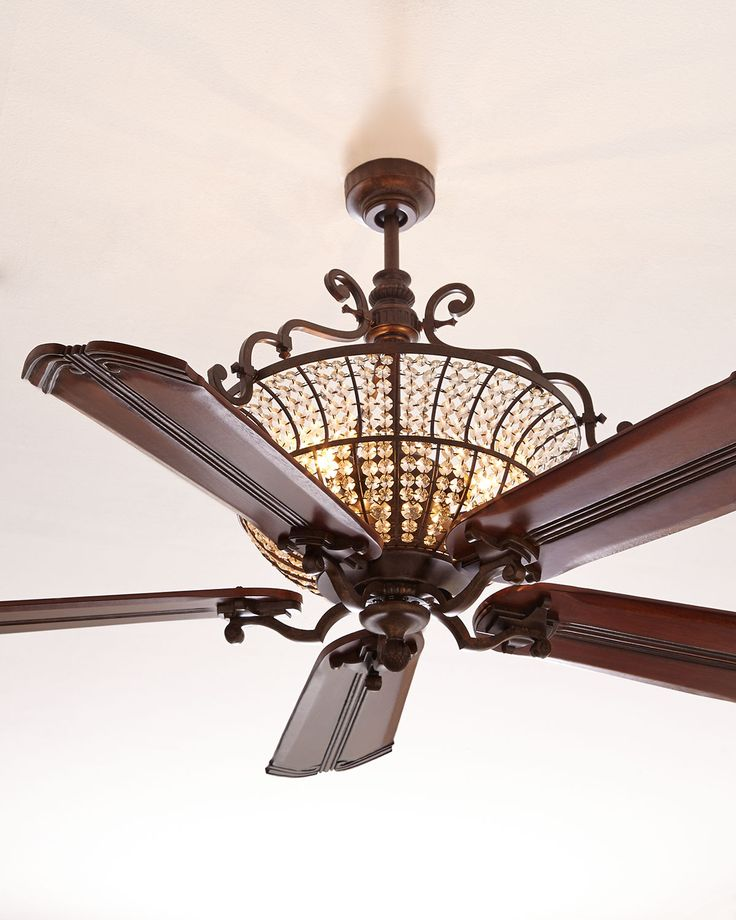 Ceiling fan features upper crystal housing with beaded, antiqued, octagon-shaped crystals and carved wood blades. Upper crystal housing has internal lighting. The beaded octagon-shaped crystals have a