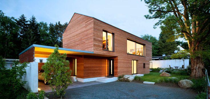 Außenansicht beleuchtet mit Carport und Garten des EFH Einfamilienhaus Wohnhaus aus Holz