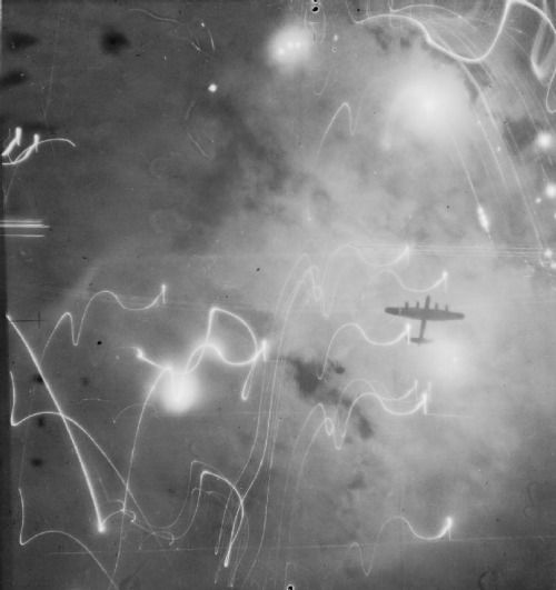 Silhouetted by smoke, flares, and explosions, this Avro Lancaster of No. 106 squadron, No. 1 group RAF takes part in the vicious attack against Hamburg, Germany. January 30/31, 1943