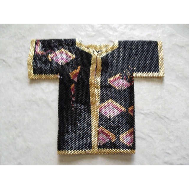 A beadwoven kimono in seed beads, that is 3 dimensional. A small doll can wear it. It is 5X6 inches and has over 11,500 seed beads.