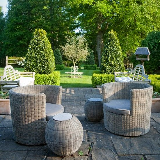 Smart rattan garden furniture creates the perfect spot to enjoy after-dinner drinks. The symmetrical topiary leads the eye out onto the lawn, which, left mostly clear, brings a formal feel to this traditional garden. Photo: Mark Bolton // Green Home