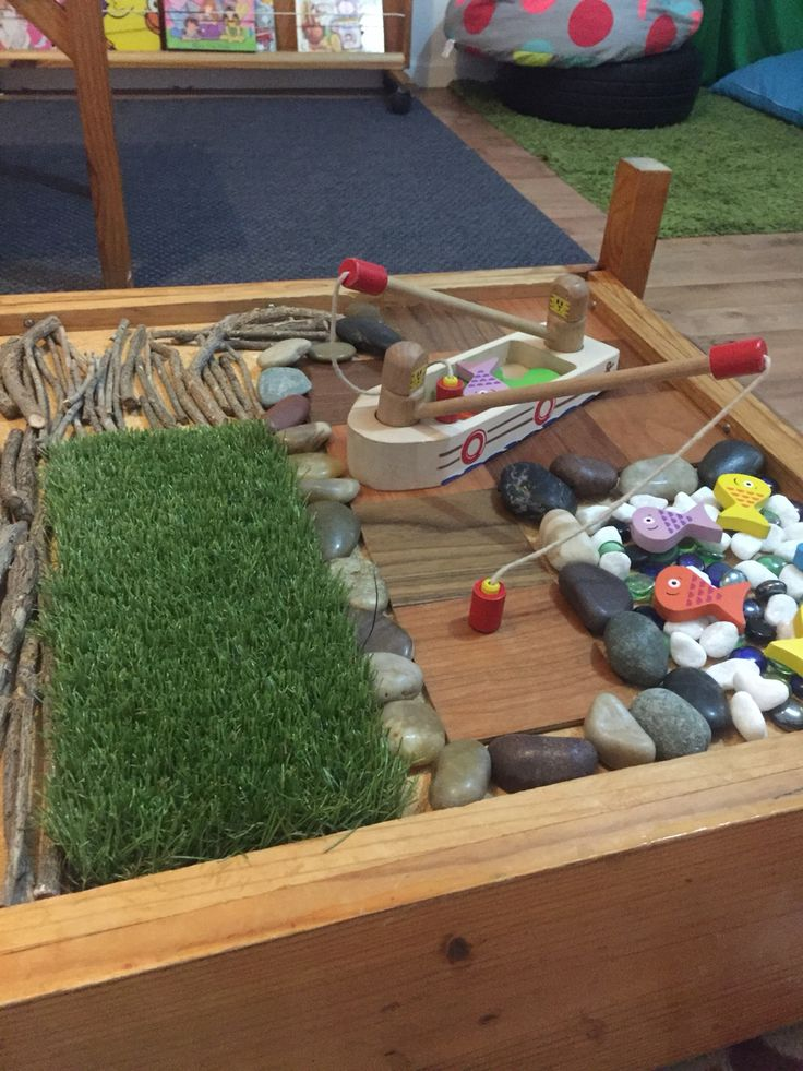 Reggio inspired table top play. Fishing theme with boardwalk and river. Magnetic fishing game for hand-eye coordination and sensory motor development.
