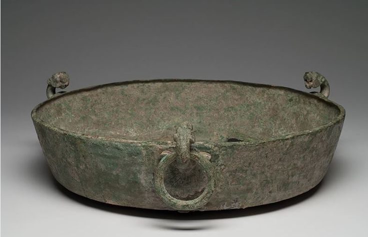 Greek bronze basin, Hellenistic period, 2nd-1st century B.C. Eastern Mediteranean. Greek bronze basin Greek cauldron having three detailed lion head handle with separate loop and large grape leaf attachments, 39.5 cm diameter. Private collection