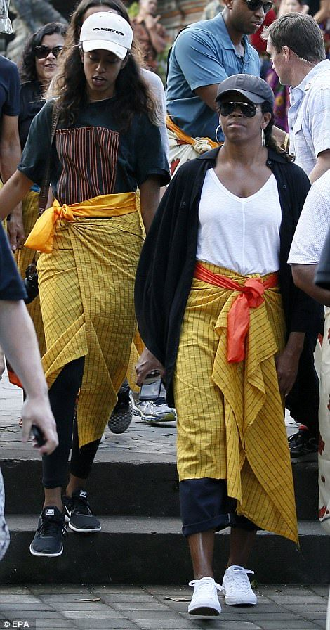Michelle, Sasha and Malia (left) wore yellow sarongs and sashes - known as a selendang - over their clothes while visiting the temple during the family holiday with Barack (right)