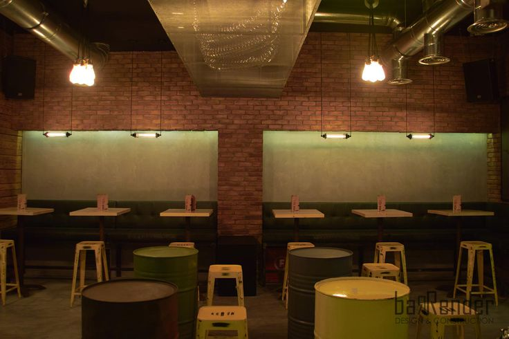 British style brickwork in combination with forged cement, wall mounted sofa with vintage cushions in cypress shade green, metal barrels as high tables in a combination of colors - Rag Doll Post modern bar in Athens.
