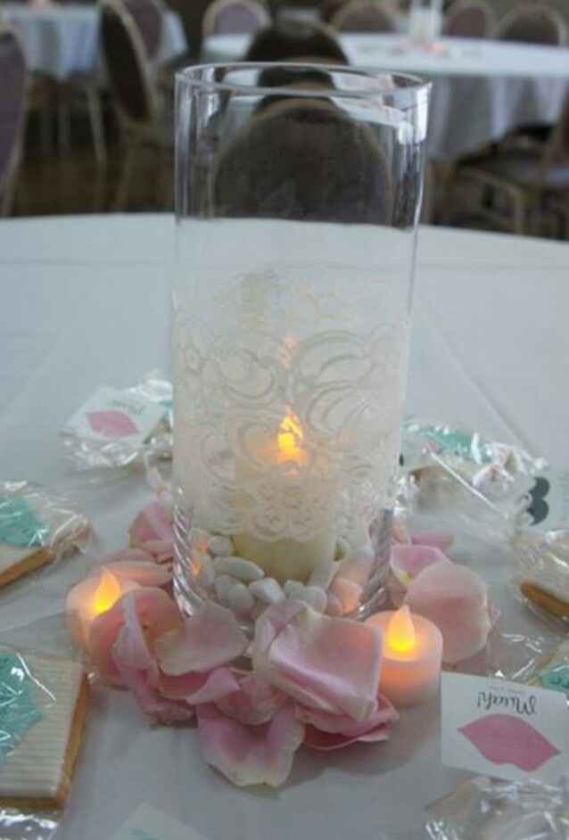 Vase with lace, candles and petals centrepiece