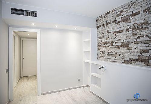 En #dormitorio principal cuenta con el detalle de una pared en ladrillo visto. #bedroom #BCN