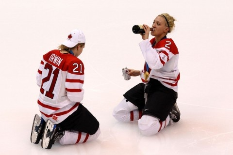 Canadian Women's hockey Olympic Gold Medalists, having a beer a centre ice after winning their medal.
