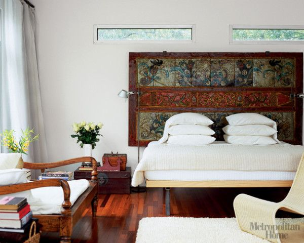 antique indonesian wall panel acts as a headboard in the master bedroom salvaged