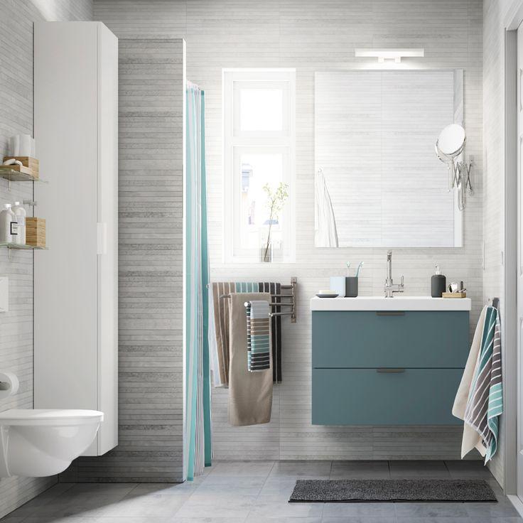 Baño pequeño de color gris claro con un armario alto blanco, un espejo y un mueble de lavabo gris con dos cajones.