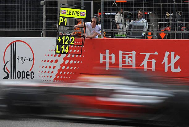 British driver Lewis Hamilton from the McLaren Mercedes team passes his pit board before winning the Chinese Grand Prix at the Shanghai International...