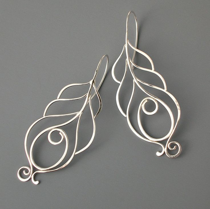 These elegant earrings are made of sterling silver. I create them by hand starting with straight wire which I shape, solder, hammer and finally polish to a high shine. They are very light weight and measure about 2 1/4 long. Comes with rubber stoppers for the back.