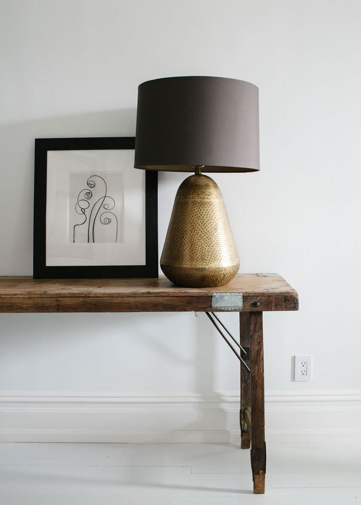 A rustic wood table finds a glamorous partner in a textured gold table lamp.