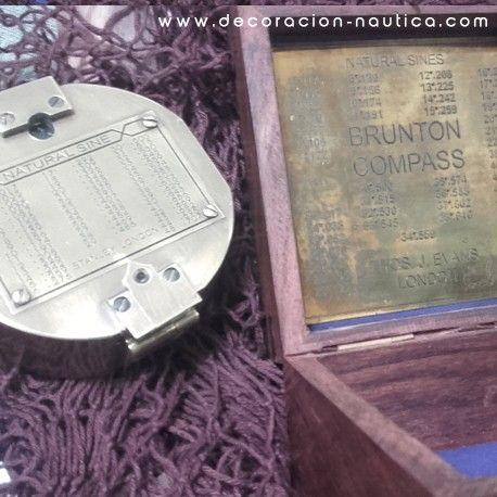 BRUJULA BRUNTON Reproducción funcional de una brújula BRUNTON inventada por el ingeniero de minas DW Brunton en 1894.  Brújula de latón viejo presentada en una hermosa caja de palisandro adornada con un ancla de laton incrustada en la madera.  Medidas: Alto: 3.00 x Largo: 7.00 x Ancho: 7.70 cm Peso: 0.65 kg