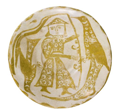 An Abbasid lustre bowl featuring a standard bearer between two birds, Iraq, 10th century composed of earthenware painted in a golden lustre on an opaque white glaze, featuring a frontal facing male figure bearing a standard between two birds on either side, all decorated with peacock eyes, with a scalloped edge design 15.2cm diam. 5.1cm height.