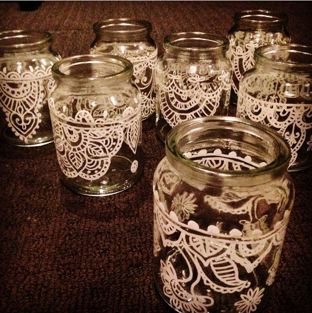 recycled coffee jars with hand drawn designs to hold a rose quartz crystal and a floating candle in each