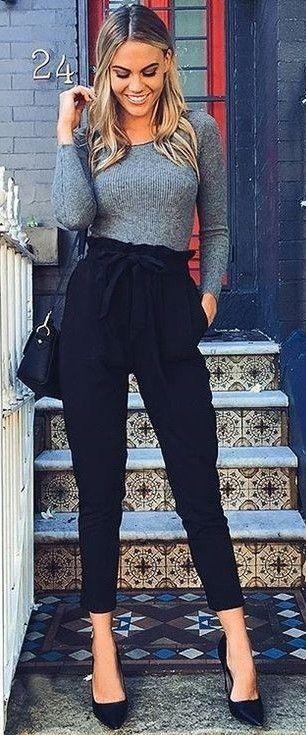 Su outfit es formal y atractivo, tiene una blusa gris formal, y un pantalón negro de tela ligera muy cómoda, lleva tacones stilleto,tiene un bolso chico color negro, su cabello esta moldeado, perfecto para una chica business casual :)