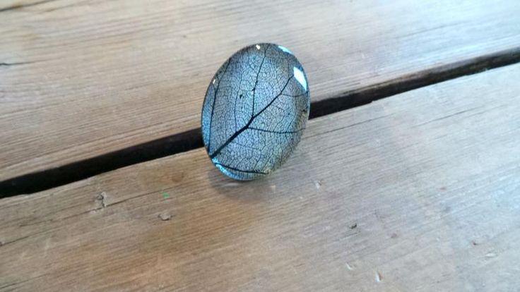 De ring heeft de afbeelding van een zwarte bladnerf tegen een wit met beige achtergrond. De afbeelding is afgewerkt met glas. De ring is koperkleurig en heeft een hoogte van 4cm en een breedte van 3cm. De ring is op elk gewenste maat verstelbaar en de ring is nikkelvrij.