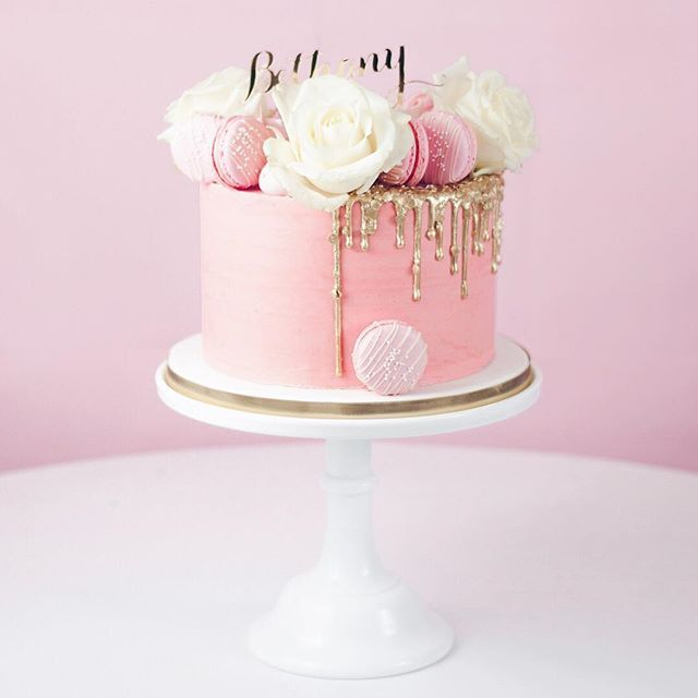 One of this weekend's cakes! One super pretty birthday cake featuring a sequin studded gold drip, large bloom white roses, our Strawberry Milkshake macarons, sprinkles and lots of vanilla meringue kisses! Happy birthday Bethany!