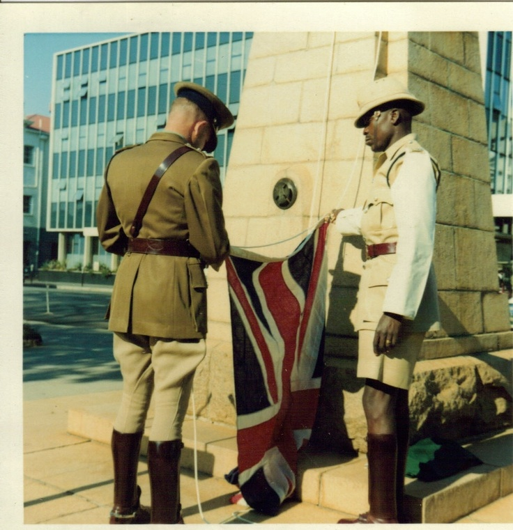 Two British South Africa Police Officers (BSAP) raise the Union Flag in Cecil Square on Pioneer Day. Salisbury, Rhodesia September 12th, 1969.