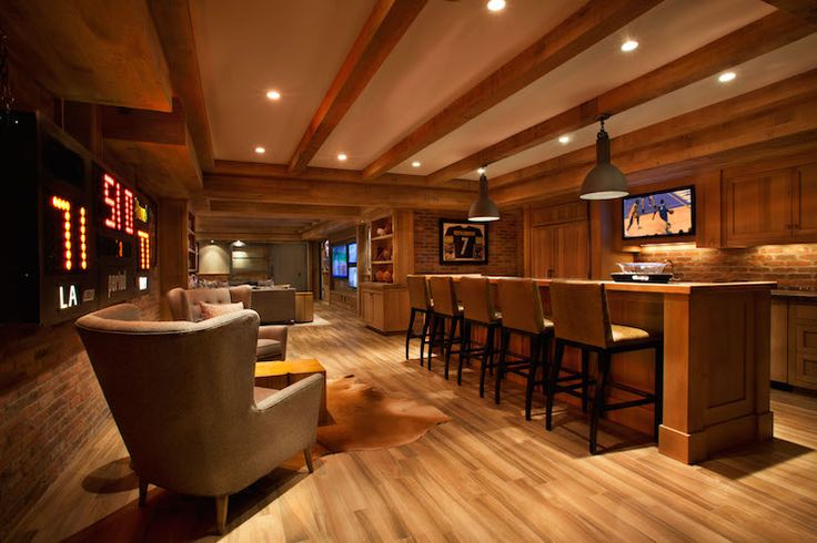Basement man cave features wood ceiling beams interspersed with pot lighting and gray industrial pendants illuminating a bar island lined with leather barstools across from rustic wood paneled refrigerator next to flatscreen TV over wet bar sink framed by stained cabinets topped with dark countertops.