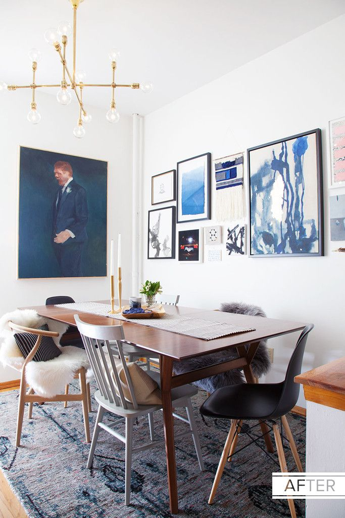 A stunning dining room with great art and mix-matched chairs.