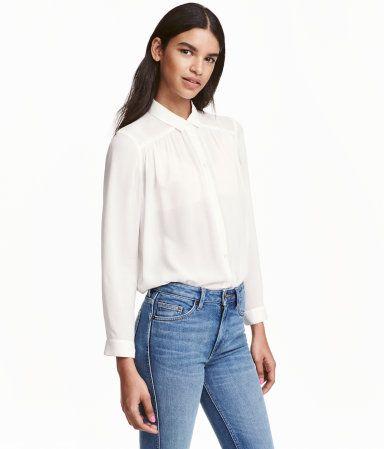 Wit. Een wijde blouse van fijne viscose met een licht onregelmatige structuur. De blouse is afgerond aan de onderkant en heeft schouderpassen met een
